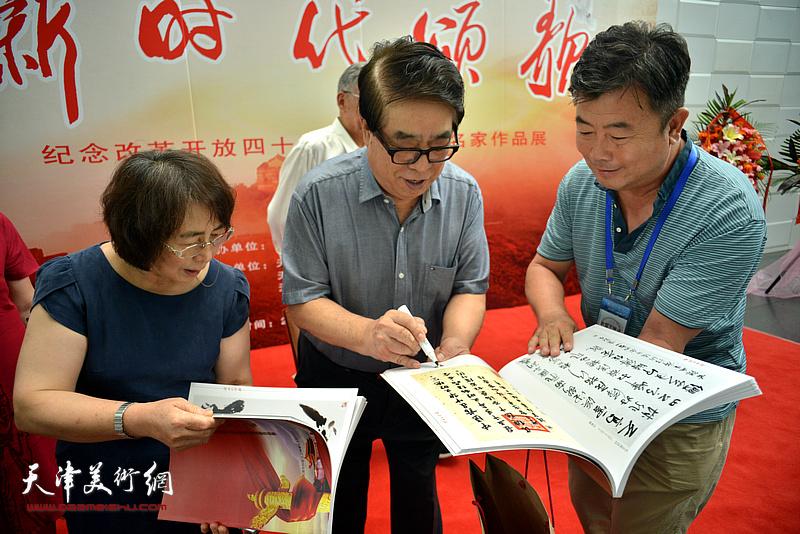 张大宁在书画展现场为观众签名留念。