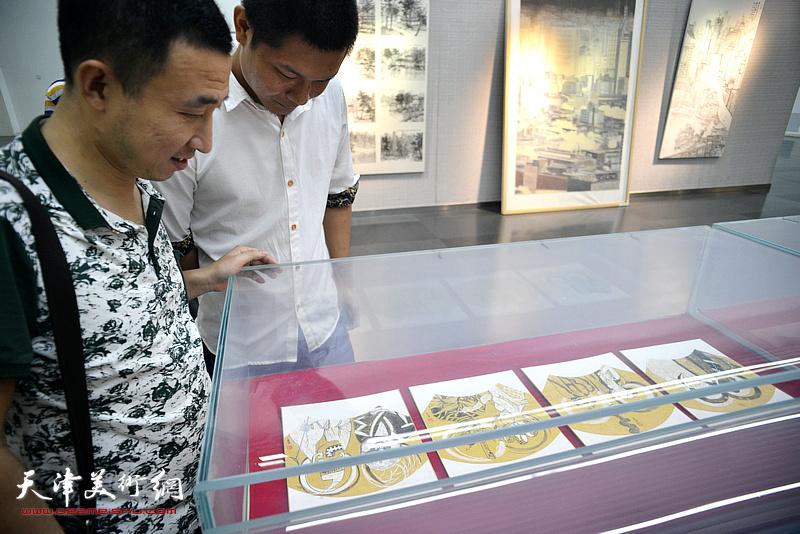 胡渤海、郑伟在画展现场观看作品。