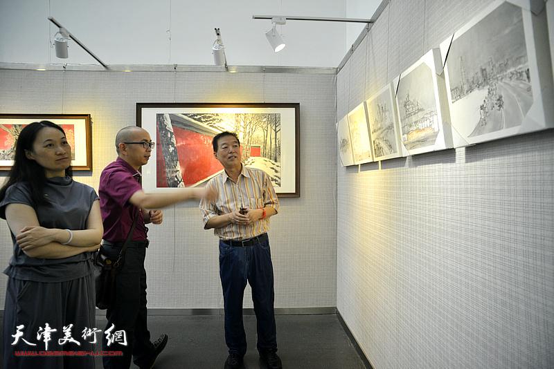 阚传好与杨建国、肖爱华观赏展出的作品。