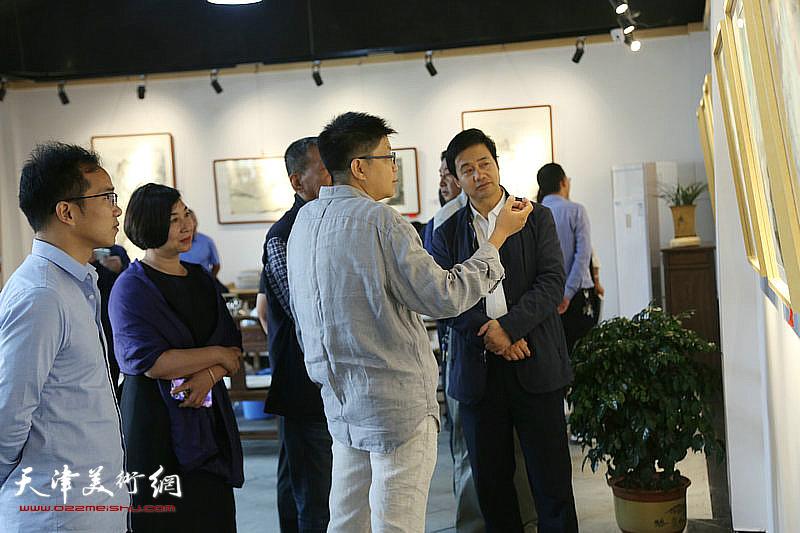李旭飞在画展现场向嘉宾讲解自己的画作。