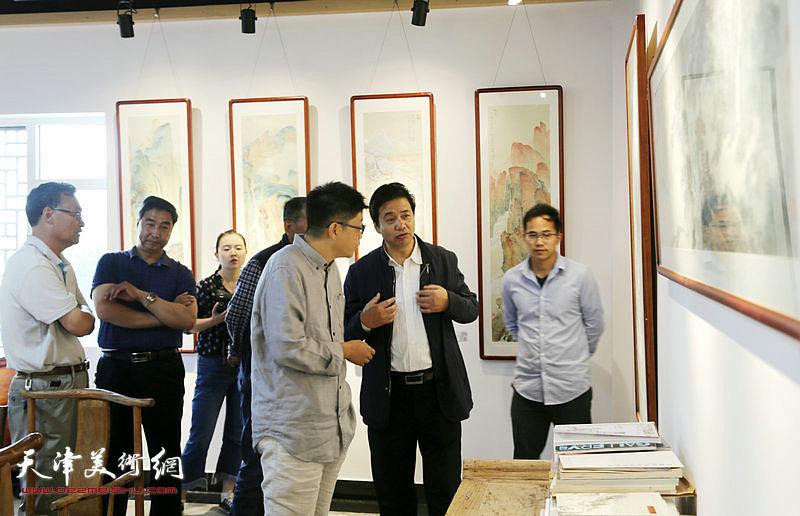 李旭飞与王升在画展现场交流。