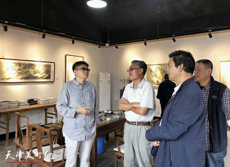李旭飞与嘉宾在画展现场交流。