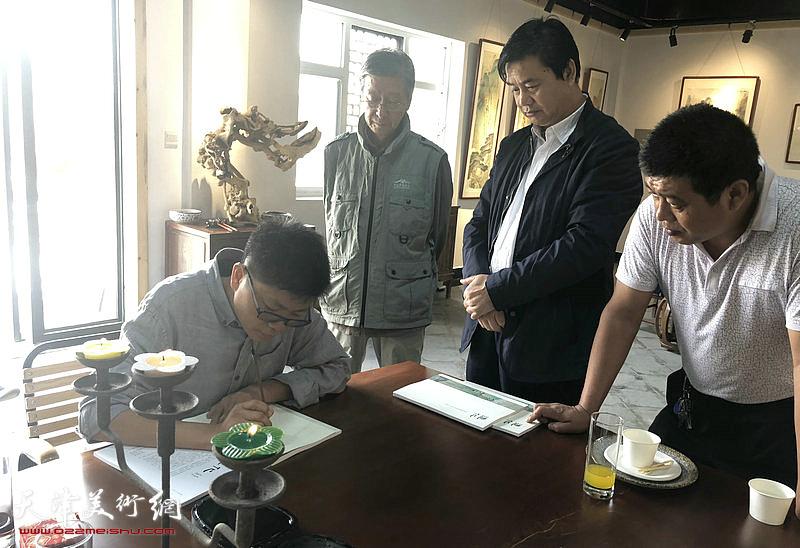 李旭飞为嘉宾在画集上签名留念。