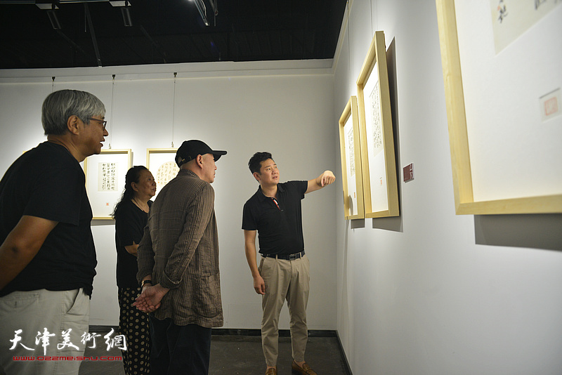 朱懿陪同孟广禄、万紫、谭志明观赏展出的作品。
