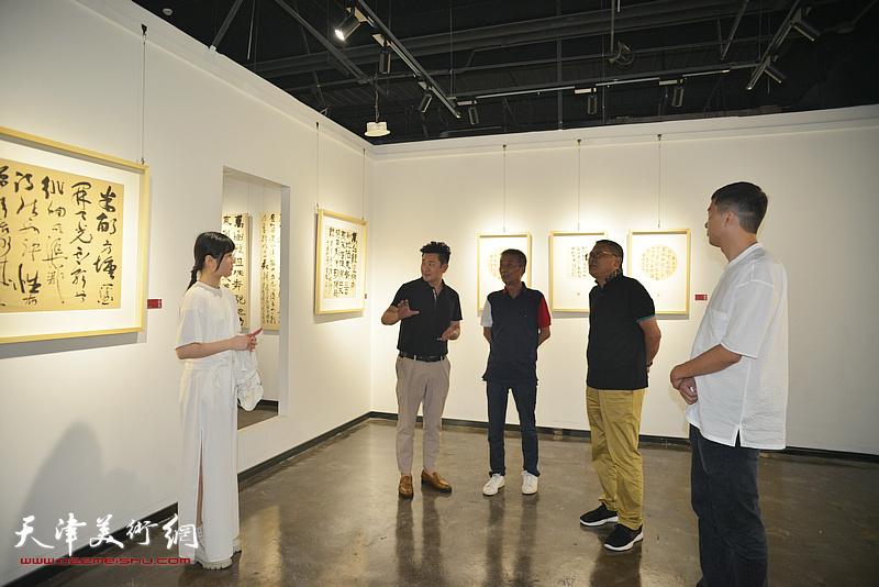 朱懿陪同邓国源观赏展出的作品。