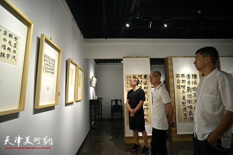 马驰、姚丽彬、朱国惠观赏展出的作品。