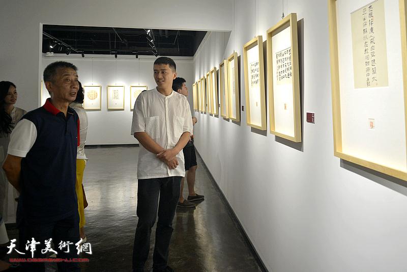 邓国源、朱国惠观赏展出的作品。