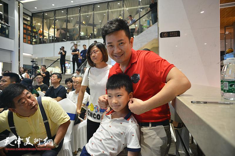 朱懿与小粉丝在作品展现场。