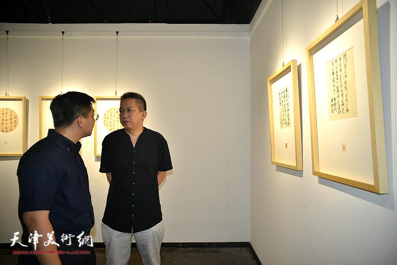 李毅峰、张耀观赏展出的作品。