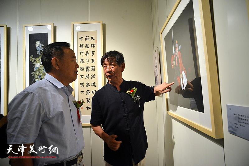 李尔山向孙辅智等嘉宾介绍画作。
