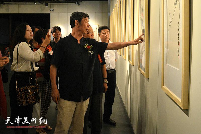 李尔山向贺锐、张养峰等嘉宾介绍画作。