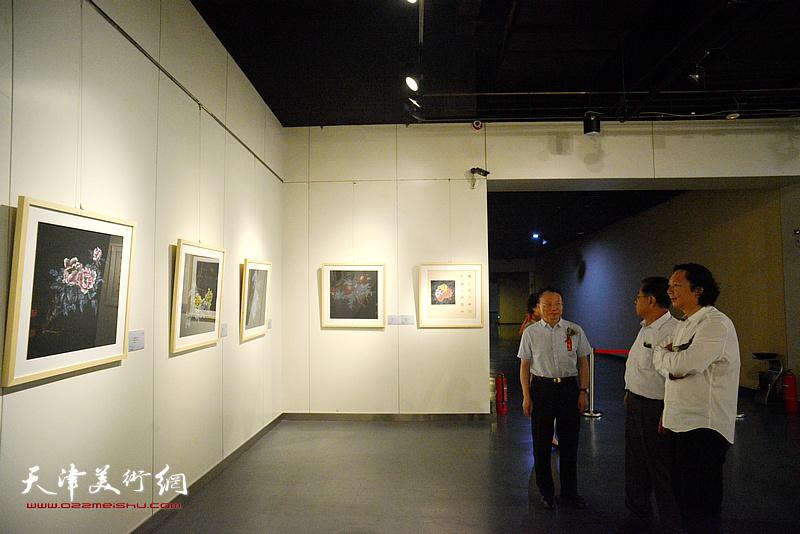 谢建华、韩必省等嘉宾观赏展出的画作。