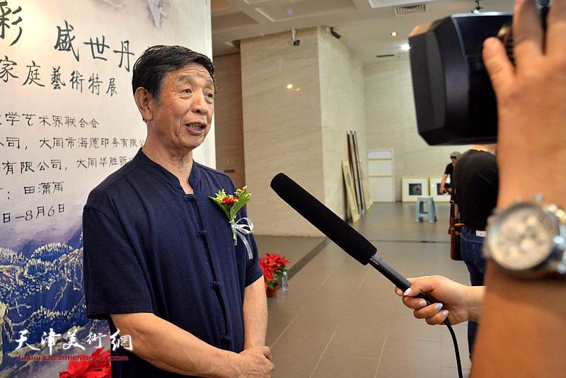 李尔山在画展现场接受媒体采访。