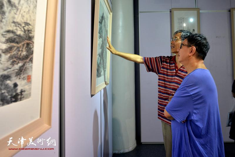 刘景樵、韩耀齐观赏展出的作品。