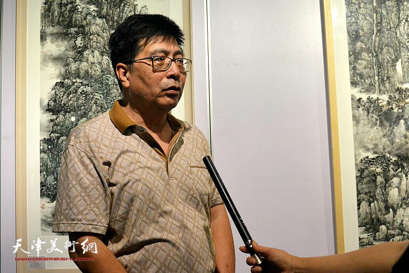 隋家祐在画展现场接受媒体的采访。
