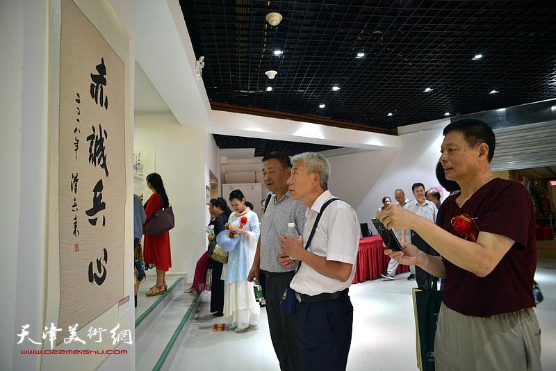 阎维海等来宾观赏展出的名家书画。