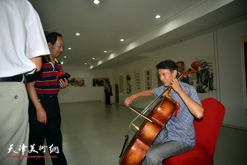 李文安在画展现场客串演奏大提琴。
