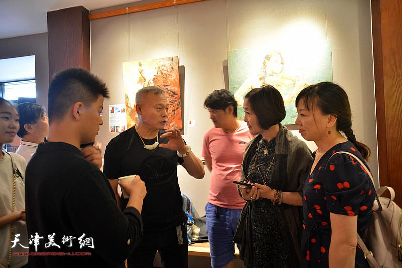 张俊国、杜雅汶等在画展现场交流。