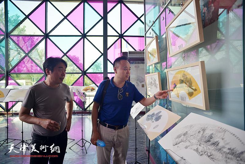 郝跃先、马明在画展现场观赏展品。