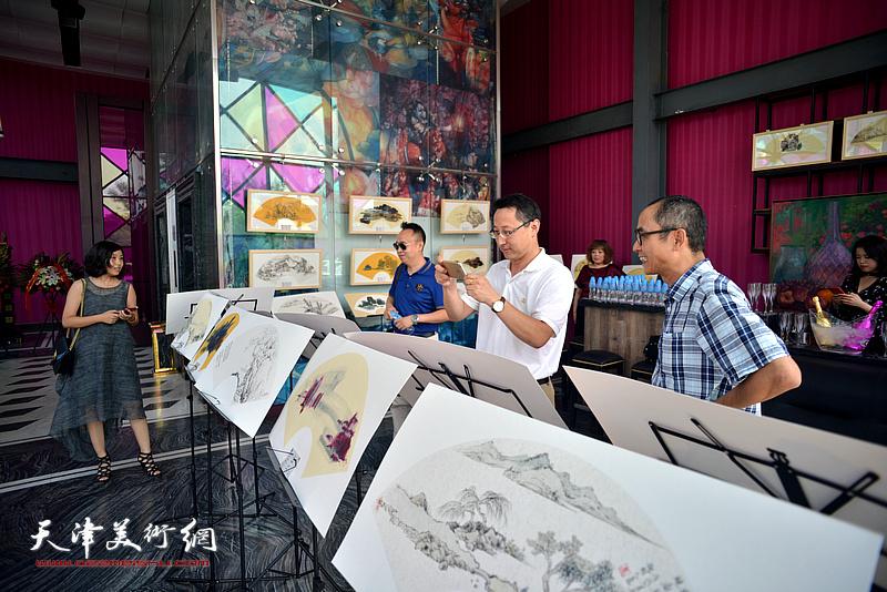 马霑与来宾在画展现场观赏展品。