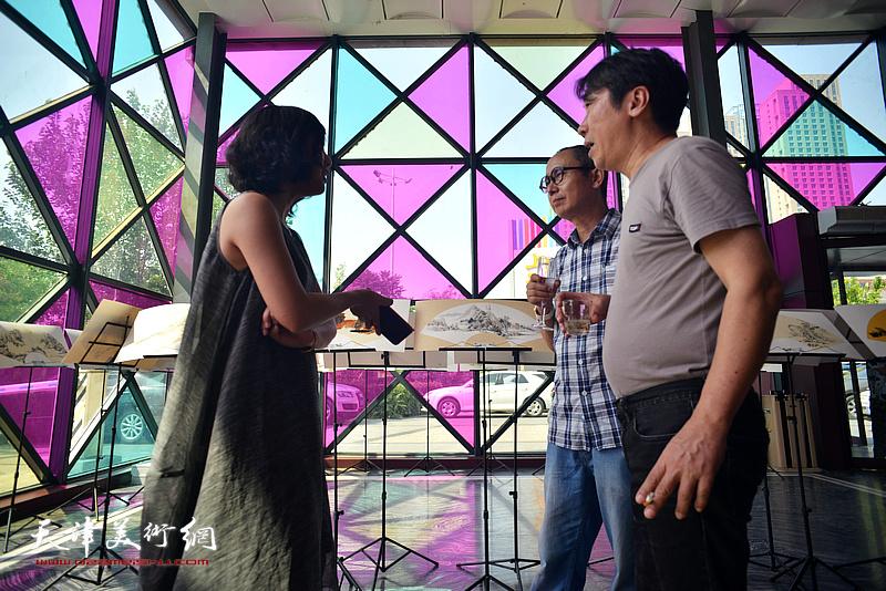 马霑、郝跃先与来宾在画展现场交流。