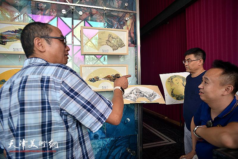 马霑、李建良、马明在画展现场交流。