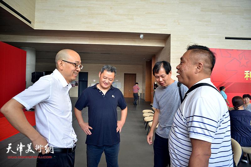 白鹏、于洪江、马驰、李伟在画展现场交流。