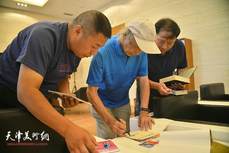 沈尧伊在画展现场为连环画藏家签名留念。