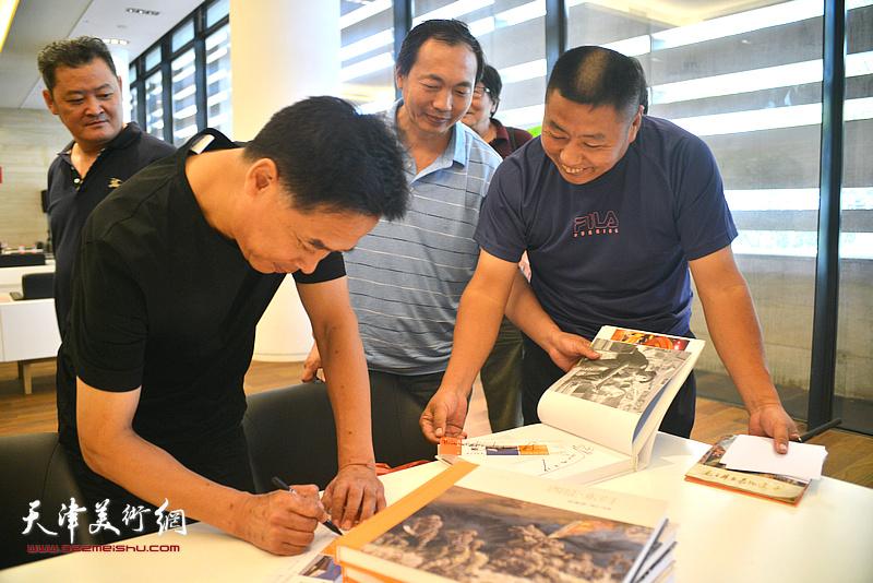 李晨在画展现场为连环画藏家签名留念。