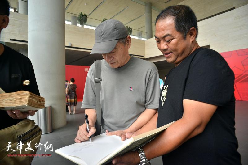 王书朋在画展现场为连环画藏家签名留念。
