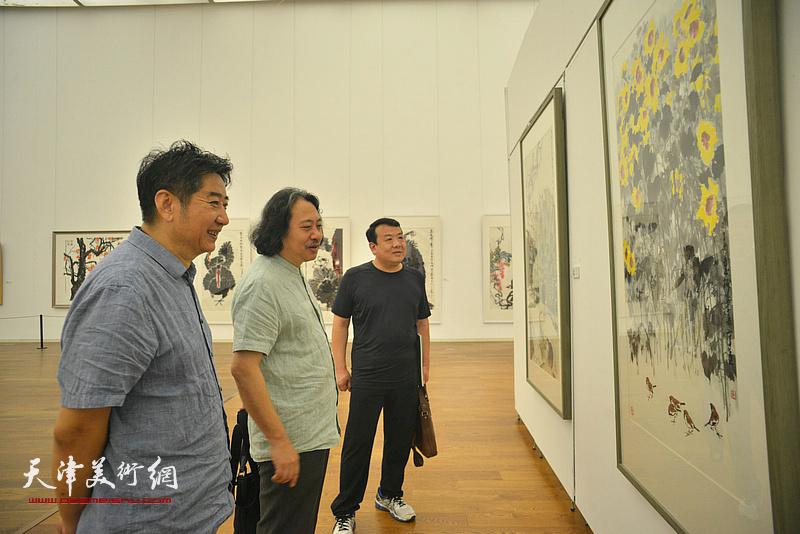 贾广健、王卫平、王爱宗观赏展出的作品。