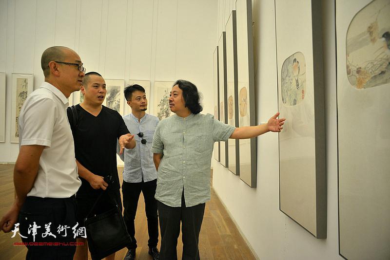 贾广健、马驰、姚丽彬观赏展出的作品。