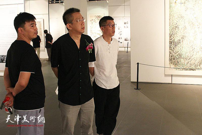 李毅峰、周明观赏展出的作品。