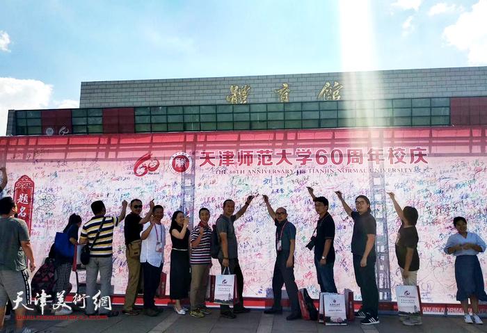图为城市画派画家在天津师范大学建校60周年纪念墙上签名。