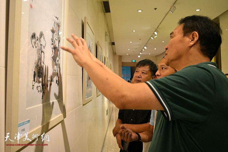 马寒松、宋新勇、姚铸在观赏展出的画作。