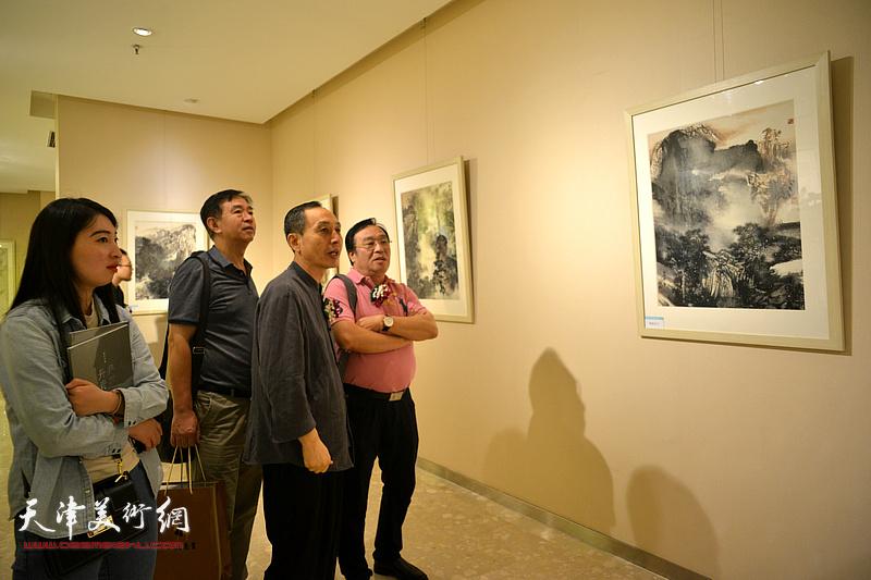 陈钢与嘉宾在观赏展出的画作。