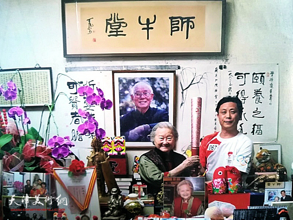 张大功与邹佩珠先生在师牛堂同举北京奥运会火炬。
