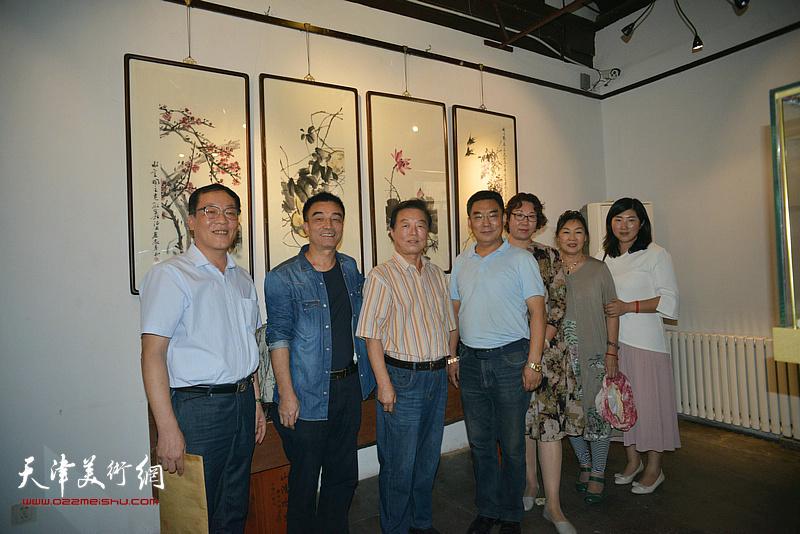 顾文忠、杨建国与来宾在画展现场。