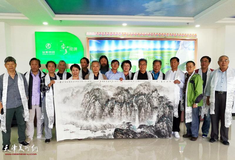 天津采风团将巨幅山水画献给安多集团。