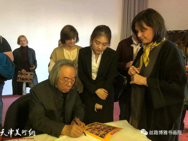 """霍春阳在""""中国画精神的内涵""""讲座现场为喜爱中国2018最新博彩白菜大全的俄罗斯大学生签名留念。"""