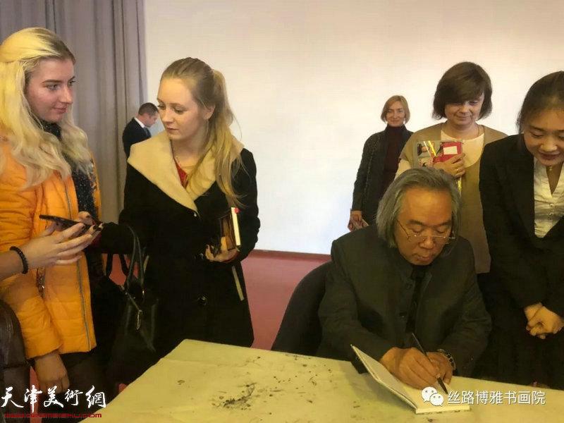 """霍春阳在""""中国画精神的内涵""""讲座现场为喜爱中国2018最新博彩白菜大全的俄罗斯师生签名留念。"""