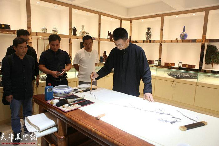 姜金军在画展现场作画。