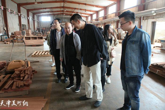 姜金军参观红木制作工艺。