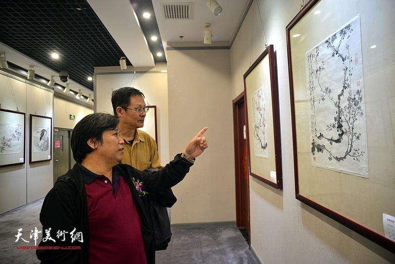 李耀春、潘津生在观赏展出的作品。