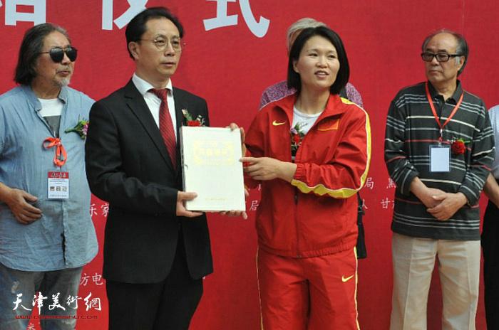 林伟宁在张大功奥林匹克收藏博物馆开馆仪式上向赠送《齐鲁撷英》奥运邮册。
