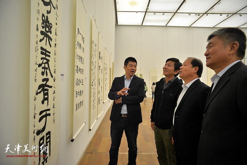 左起:薛卫林、李锋、王印强、潘津生在展览现场观看作品。