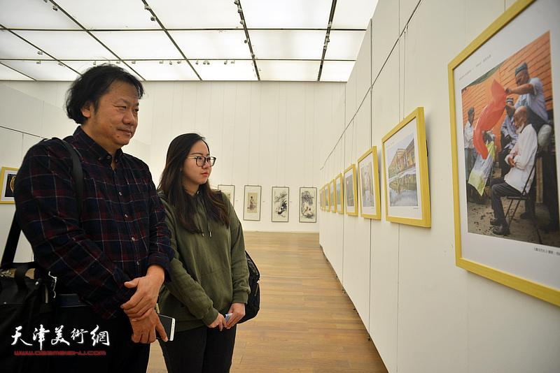 艾德胜、艾梦在展览现场观看作品。