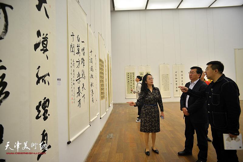 卢永琇陪同烟台客人在展览现场观看作品。