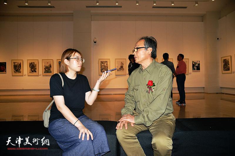陈福春在画展现场接受媒体采访。
