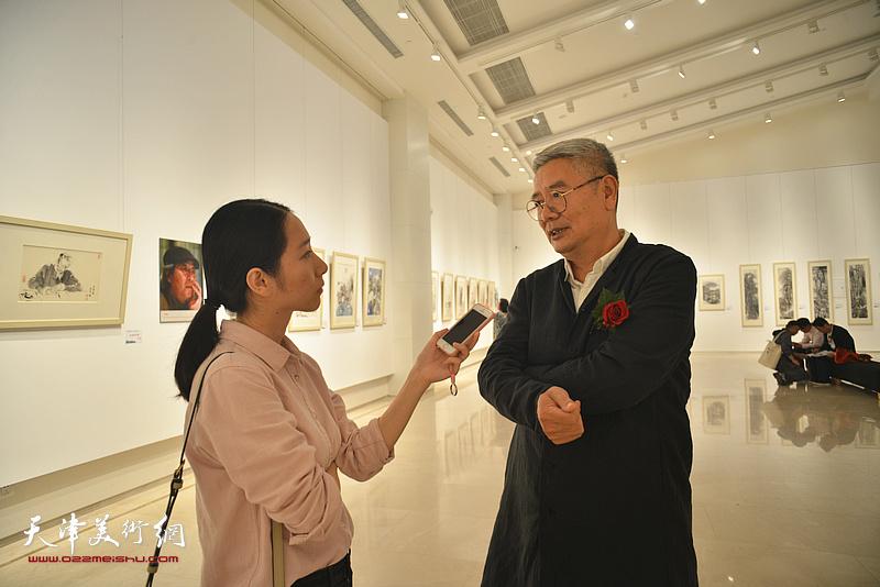 张佩钢在画展现场接受媒体采访。
